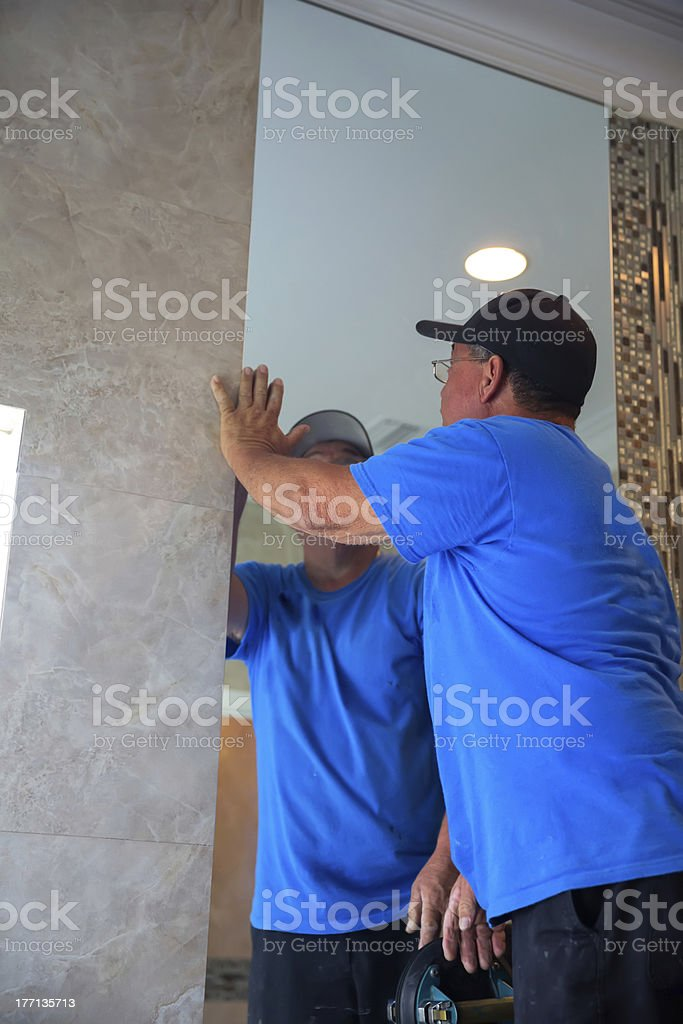 Workman installs mirror in master bathroom royalty-free stock photo