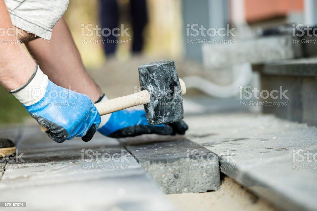 Workman laying a paving stone or brick stock photo
