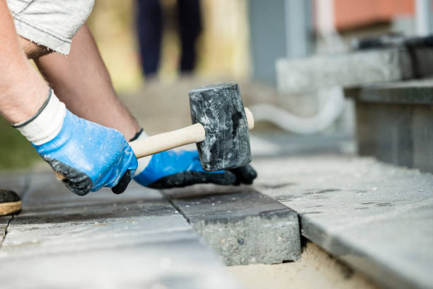 Workman laying a paving stone or brick stock photo