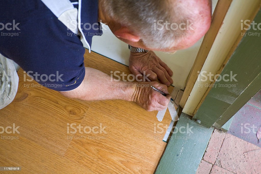 Workman laying timber flooring stock photo