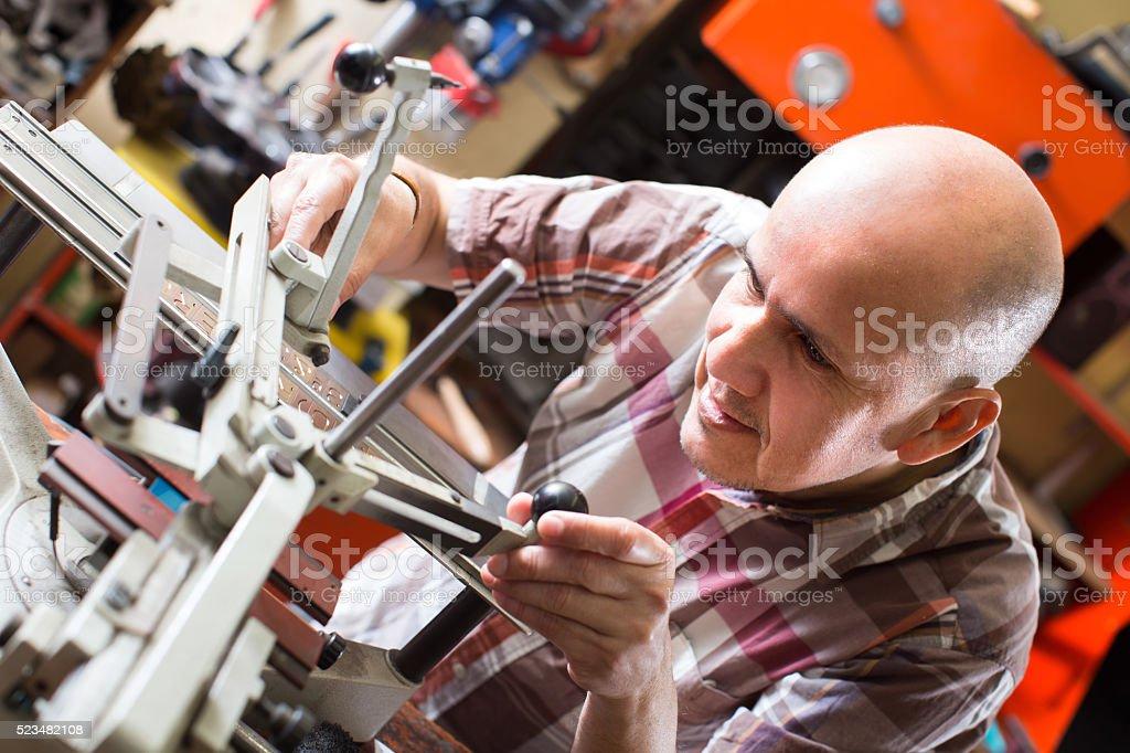 Workman making mailbox plate in workshop stock photo