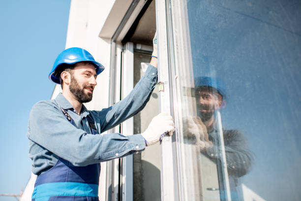 Workman mounting windows Workman in uniform mounting windows checking the level on the white building facade replacement stock pictures, royalty-free photos & images