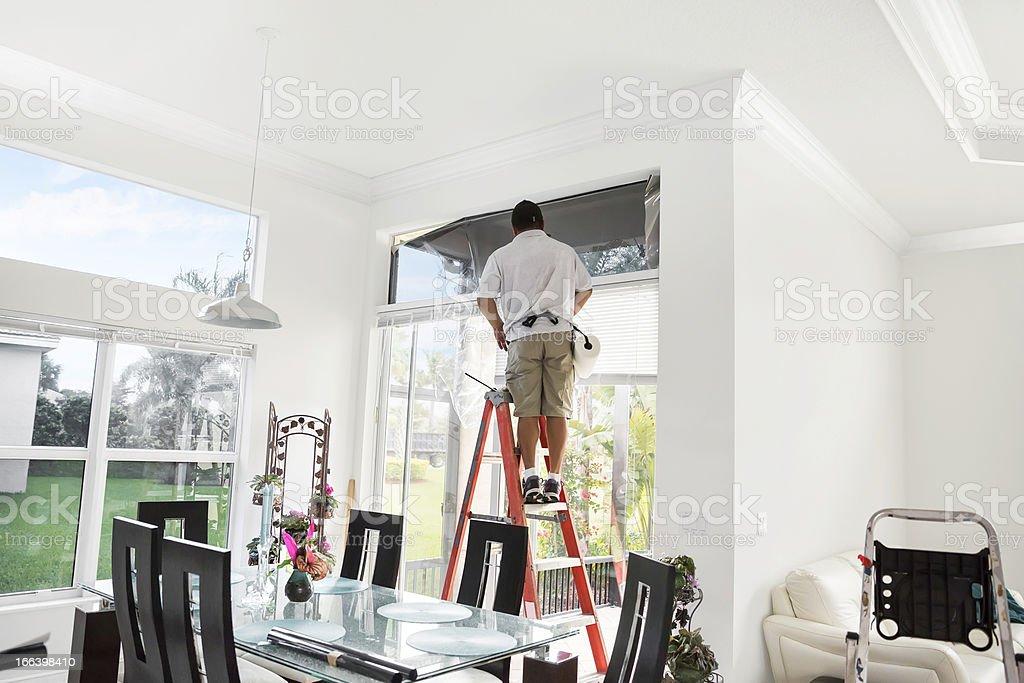 Workman on ladder adding tinting to upper, interior window royalty-free stock photo