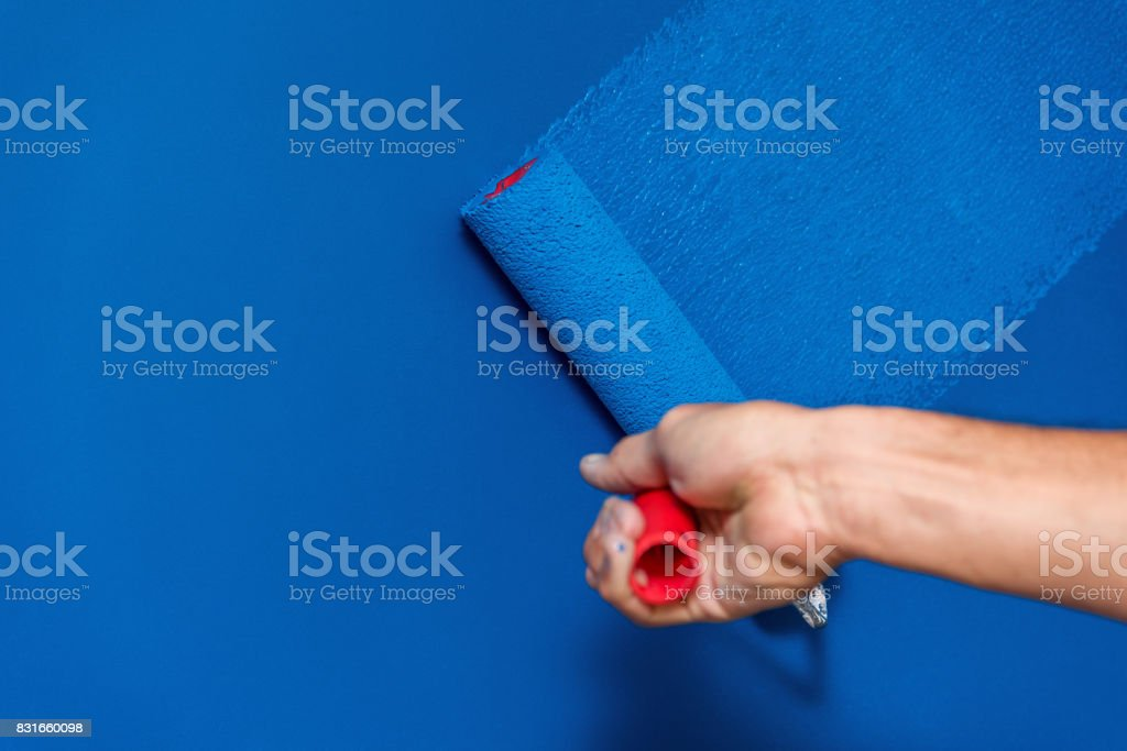 workman painting the wall in blue stock photo