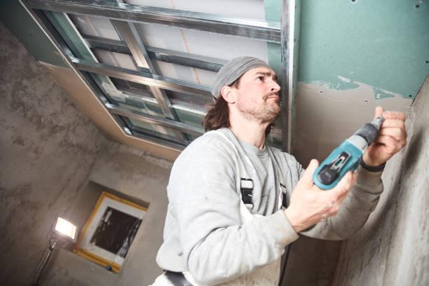 Workman plastering gypsum walls inside the house. stock photo