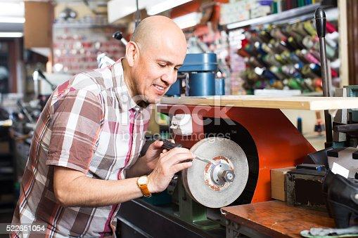istock Workman resharpening knives on machine 522651054