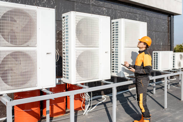 Workman servicing air conditioning or heat pump with digital tablet stock photo