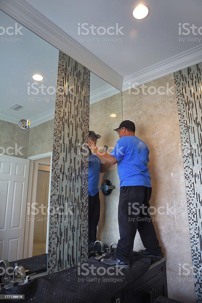 Workman standing on bathroom vanity to install mirror royalty-free stock photo