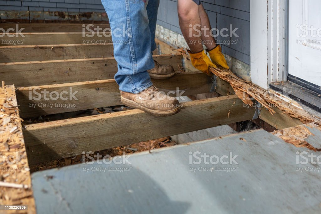 Workman Standing on joists of rotten deck removing rotted wood stock photo