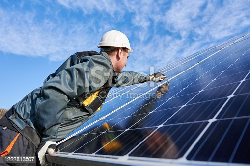 Side view snapshot of workman, wearing uniform, working gloves and helmet, setting a shiny new solar battery with help of hex key, blue sky on background. Green energy concept