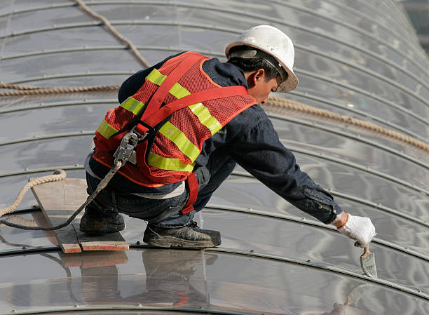 Workman with safety harness A workman painting the steel girders of a curved perspex roof wearing a safety harness. safety harness stock pictures, royalty-free photos & images