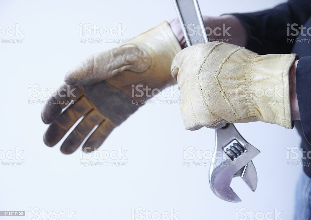 Workman with tool pulls on gloves stock photo