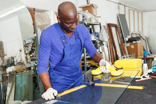 arbeiter, die arbeit mit glas in werkstatt - fensterbauer stock-fotos und bilder