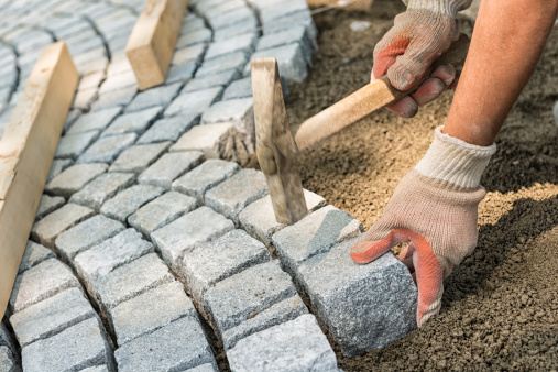 istock A workman's gloved hands use a hammer to place stone pavers 181091732