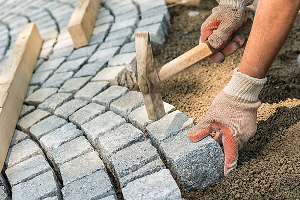 A workman's gloved hands use a hammer to place stone pavers stock photo