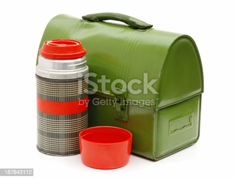 Workman's vintage lunchbox and thermos. Green dented metal lunchbox and open red and silver thermos on white background.