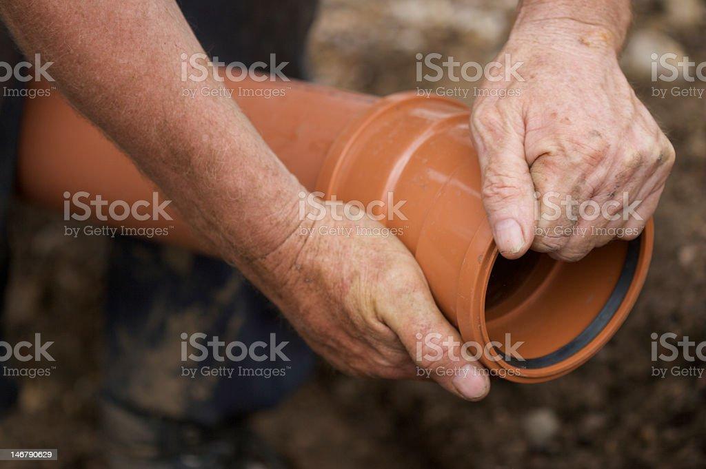 Workmen Holding PVC Drainpipe stock photo