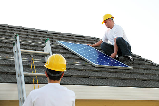 Workmen Installing A Solar Panel stock photo