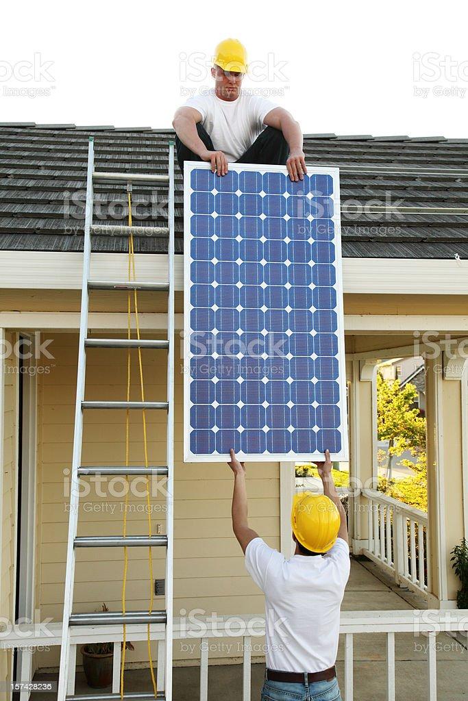 Workmen Lifting A Solar Panel royalty-free stock photo