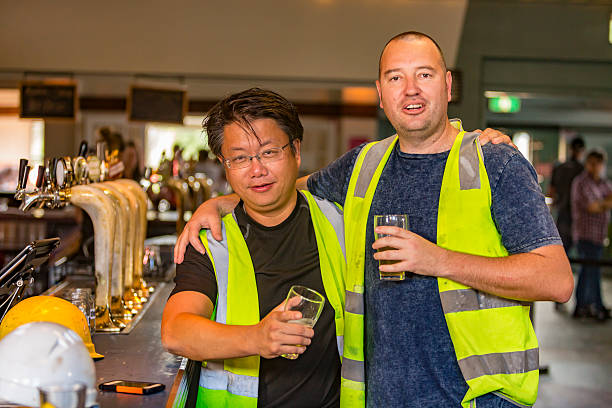 Workmen Relaxing With Beer After Work in High Visibility Clothes stock photo