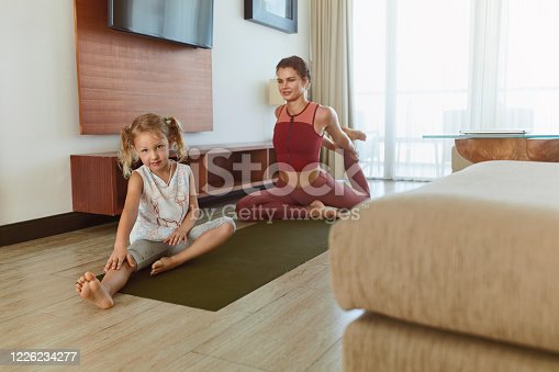 916126642 istock photo Workout At Home. Mother And Daughter Exercising Together In Living Room. Little Girl And Young Woman Practicing On Yoga Mat. Sport Routine For Active Lifestyle. 1226234277