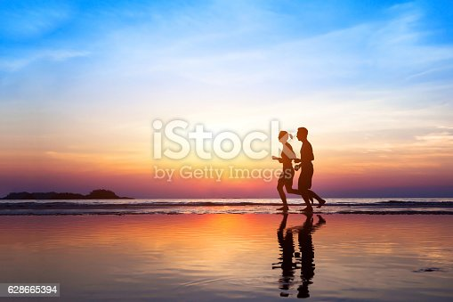 istock workout background, two people jogging on the beach 628665394