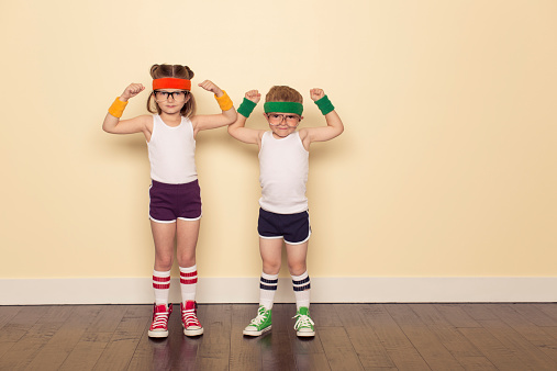 A boy and girl dressed as 80s nerds are ready to sweat to stay fit during this workout. Flex your biceps for ultimate self confidence.