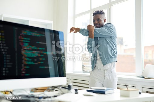 Young it-manager in casualwear standing between window and his desk with computer and doing exercise for arms
