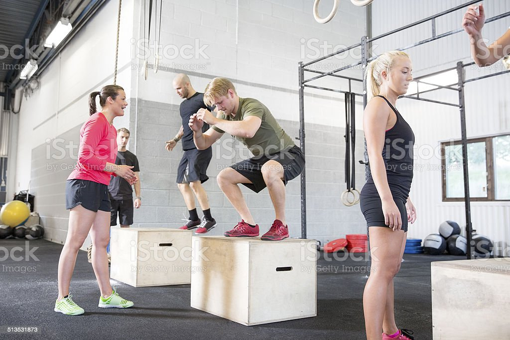 Workout group trains box jumps stock photo