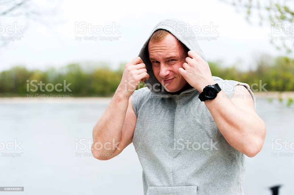 Workout man in hood resting by the river outdoor. stock photo