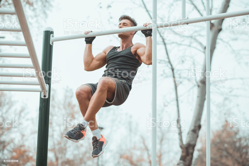 Workout man with sports gloves doing chin-ups stock photo
