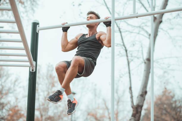 training-mann mit sporthandschuhe klimmzüge zu tun - straßentraining stock-fotos und bilder