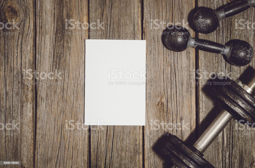 workout plan background dumbbells on wooden gym floor or table stock