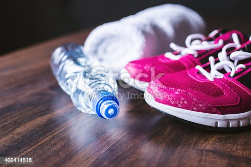 istock Workout shoes, water bottle, and towel on wooden background 466414818