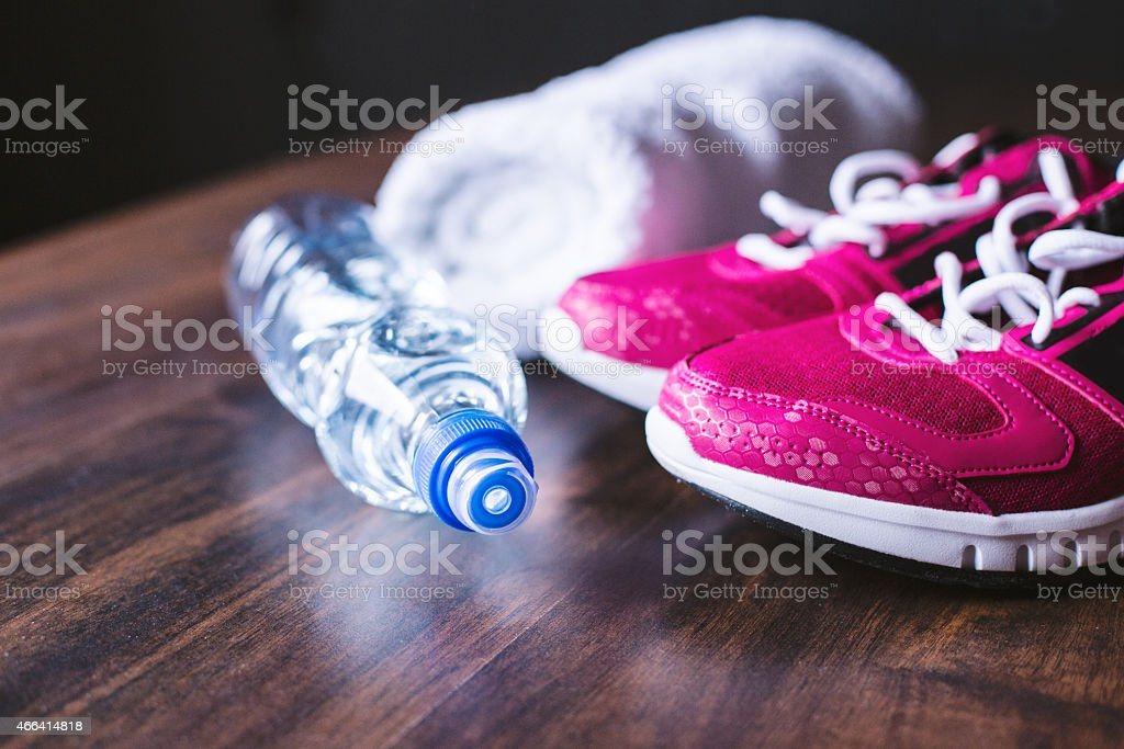 Workout shoes, water bottle, and towel on wooden background stock photo