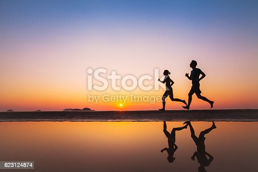 istock workout, silhouettes of two runners on the beach 623124874