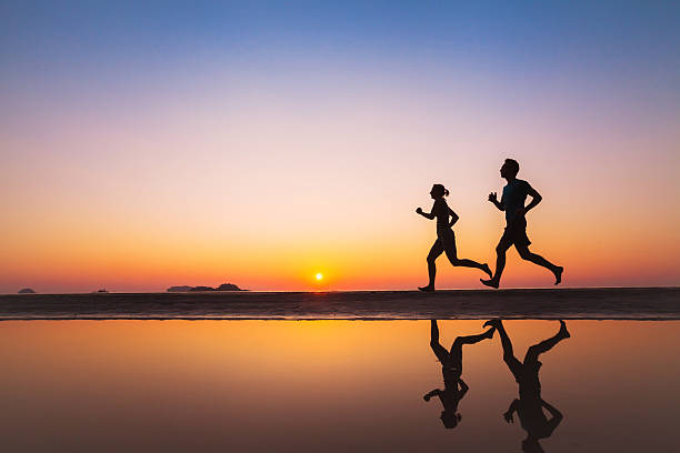 workout, silhouettes of two runners on the beach stock photo