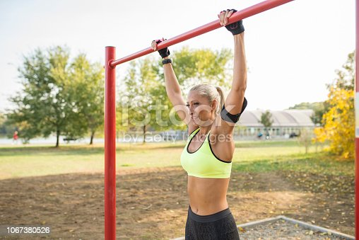 Attractive blonde sportswoman exercising on horizontal bar in the public park. Healthy lifestyle concept.