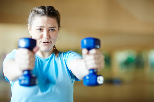 Workout with dumbbells Young female in blue t-shirt doing effective exercise with dumbbells while working out in gym body positive stock pictures, royalty-free photos & images