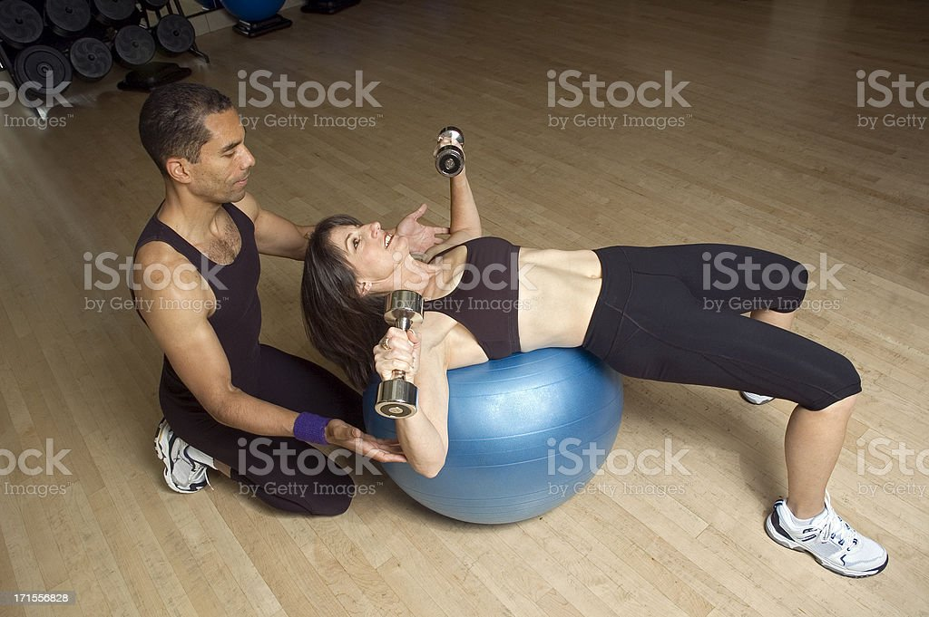 Workout with Exercise Ball and Trainer royalty-free stock photo