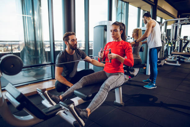 Workout with personal trainer on rowing machine at gym stock photo