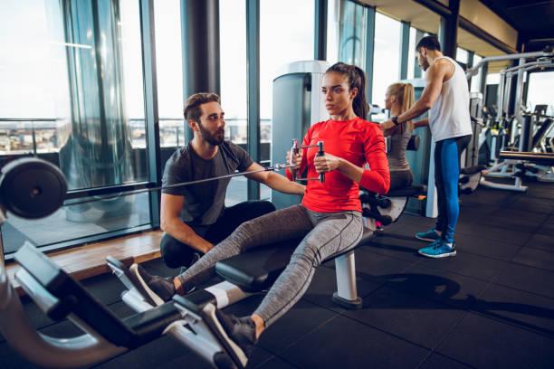 entrenamiento con entrenador personal en la máquina de remo en el gimnasio - entrenador personal fotografías e imágenes de stock