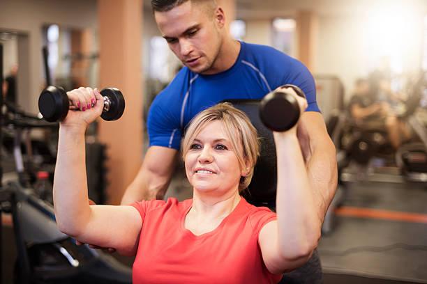 Haga ejercicio con un entrenador personal. - foto de stock