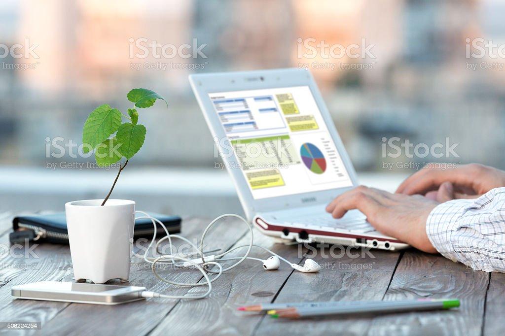 職場での屋外パティオで木製テーブルコンピューターと花 ストックフォト
