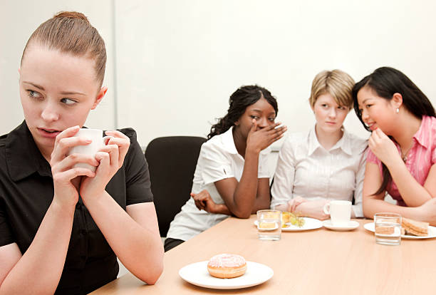 Workplace Bullying A young woman sits along at coffee break as her co workers gossip behind her back.  Shallow depth of field - focus on the excluded model in the foreground.Click cruel stock pictures, royalty-free photos & images