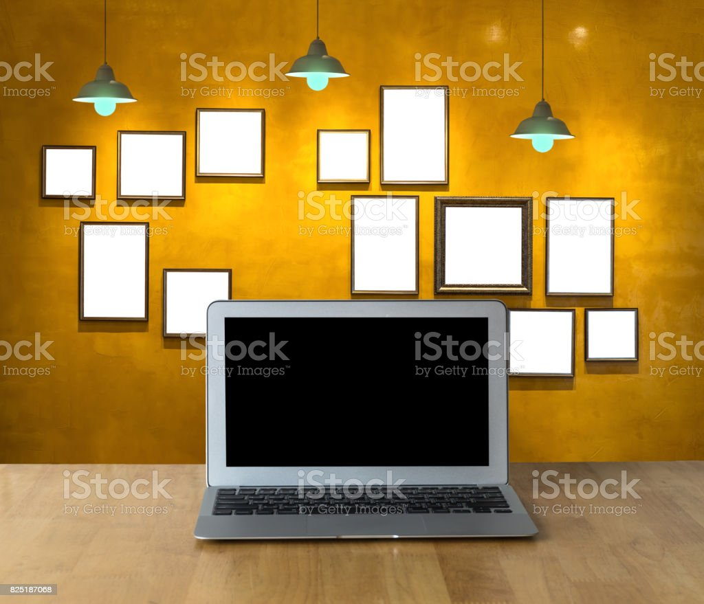 Workplace computer laptop on wooden table and Vintage wall background and seat with photo frame and light, Interior gallery stock photo