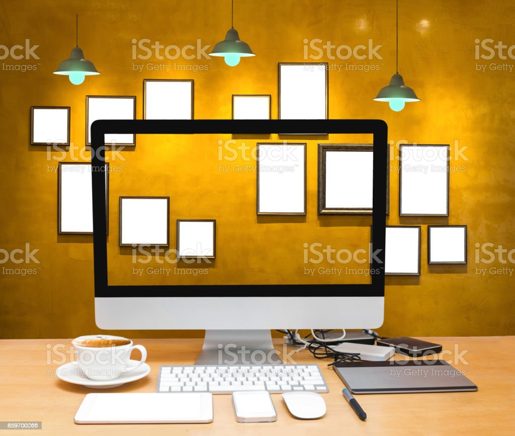 Workplace computer laptop with coffee cup on wooden table and Vintage wall background and seat with photo frame and light, Interior gallery stock photo
