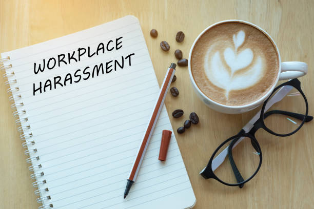 Workplace harassment concept on notebook with glasses, pencil and coffee cup on wooden table. Business concept. stock photo