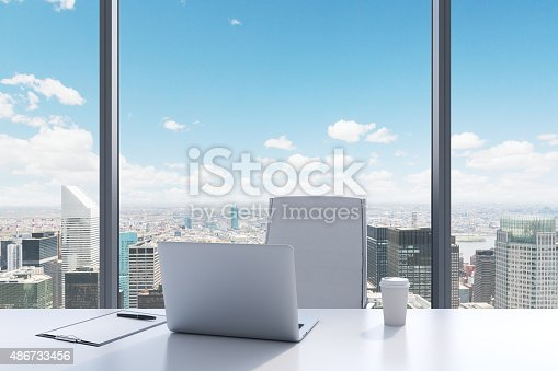 A workplace in a modern panoramic office with New York view. A white table, white leather chair. Laptop, writing pad and a cap of coffee are on the table. Office interior. 3D rendering.