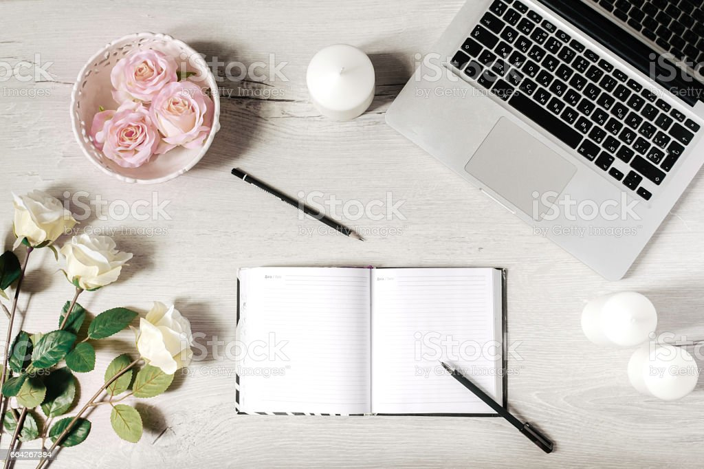 Workplace in modern style with laptop, diary, white candles, roses and wooden desk. Flat lay stock photo